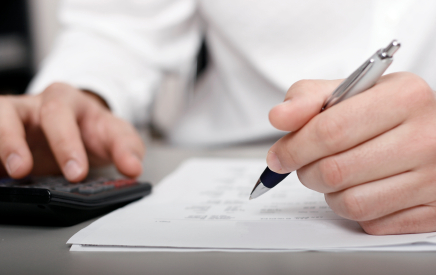 cost to create e-learning - photo of pen, paper, hand, and calculator