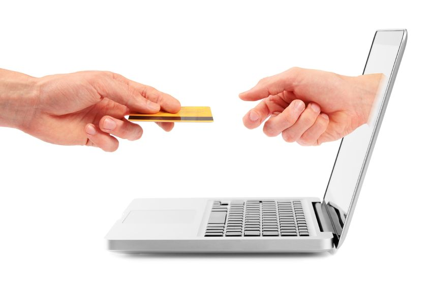 transactions vs relationships - photo of two hands exchanging cedit card through laptop screen